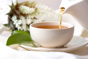 Poster de jardin The Close up pouring hot black tea in a white tea cup , Tea ceremony time concept