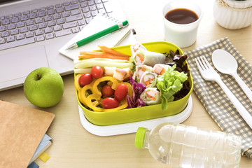 Close up green Lunch box on the work place of working desk ,Healthy eating clean food habits for diet and health care concept