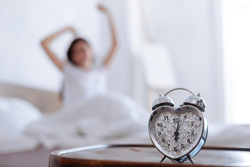 Close up of alarm clock ringing and woman stretching behind