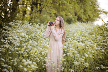 Dreamy relaxed and happy teenager girl taking photo with old camera, walk in the blooming meadow surrounded by white flowers of ground elder in the magic light of sunset in vintage linen dress