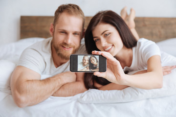 Portrait of newly married couple taking selfie in bed