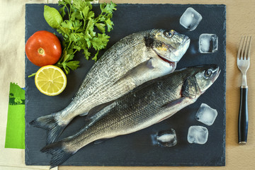 Two ready to cook raw fish with vegetables on stone slate board.