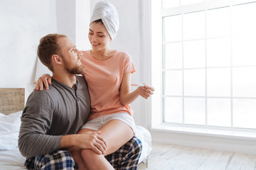 Happy pregnant woman sitting on husbands lap