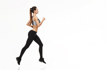 Beautiful sportive girl in sportswear training running over white background. Copy space.