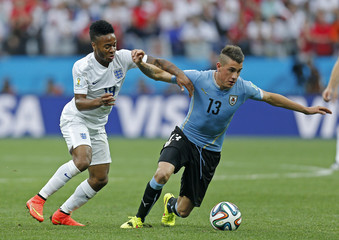 England's Raheem Sterling (L) and Uruguay's Jose Gimenez in action