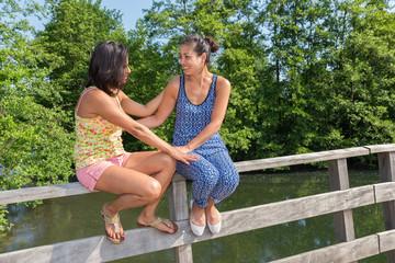 Two friends sitting together on bridge railing