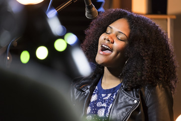 Black female singing in a recording studio Fotobehang