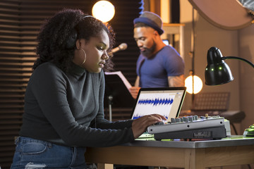 Black male vocalist working with sound engineer in a recording studio