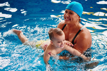 Healthy family, mother teaching baby swimming pool