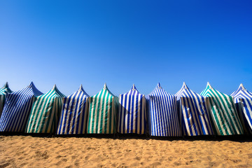 sunshades in beach at summer against blue sky
