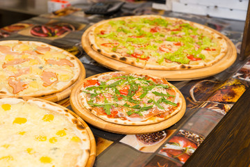 Tasty pizzas with variety of toppings and cheese on wooden trays