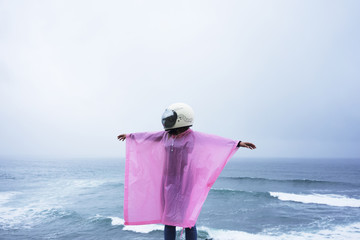Unrecognizable girl in pink rain coat and white helmet stands above blue ocean and spreads her arms around under rain in fog day.