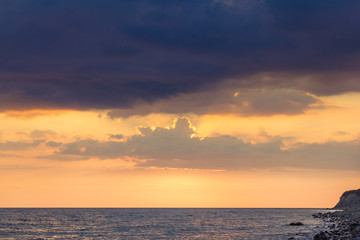 Beautiful sunset among the unimaginable clouds with glimpses of rays on the sea