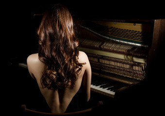 beautiful young woman in a black dress with an open back sitting nere the piano on a dark background