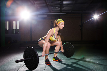 A beautiful young girl in the gym trains the muscles of the legs and back, deaet exercises deadlift, sits with weight, holds bar in her hands