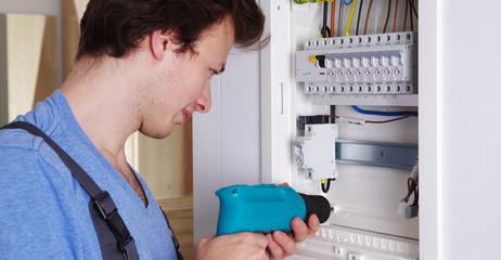 Ein Elektriker bei der Arbeit an einem Sicherungskasten