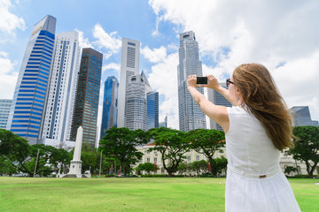 Girl with a smartphone taking a picture of amazing cityscape
