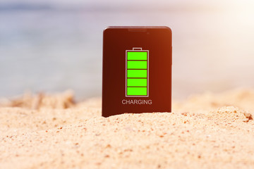 The smartphone is stuck in the sand on the beach and is charging. The concept of recharging during the holidays. Rest on the sea. Relaxation. The background