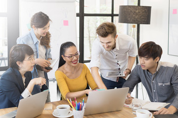 Multiethnic diverse group of creative team, casual business people in strategic meeting or project brainstorm discussion at office, using smartphone laptop and tablet. Startup or teamwork concept.
