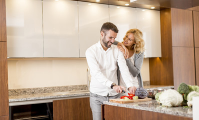 Man helping his girlfriend cooking in modern kitchen