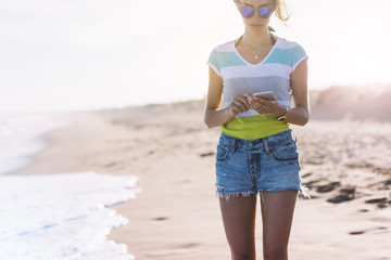 Hipster girl photograph on smart phone gadget in sand coastline beach, mock up. Traveler hold and using in female hand mobile on background seascape horizon. Tourist look on blue sun ocean