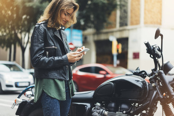 Fotomurales - Girl in leather jacket holding smart phone on background motorcycle in sun city, hipster using in female hands and texting mobile, street lifestyle, tourist planing route in summer concept