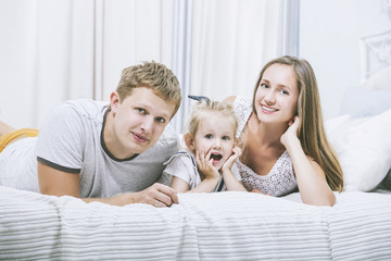 Happy beautiful young family father, mother and daughter  smiling together at home