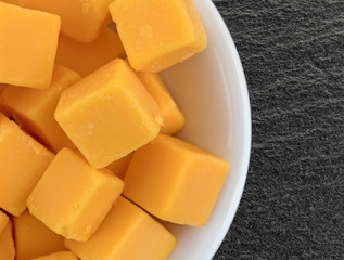 Cubed mild cheddar cheese in a white bowl atop a black slate table top.