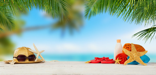 Tropical beach with accessories on sand, summer holiday background.