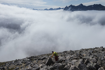 Hiker on rocky mountain side approaching cloud covering valley