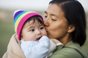 Portrait of woman kissing baby girl
