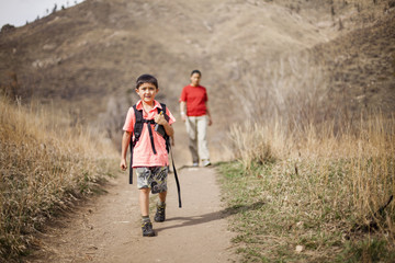 Boy hiking on dirt path along Hewlett Gulch Trail with mother in distance