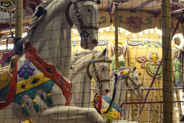 Close up view of horses of a carousel in front of Hotel De Ville Paris. Childhood, nostalgic fun concept.