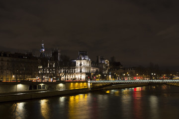 View of long exposed Seine river and historical architecture buildings in Paris at night in winter.