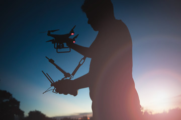 Man playing with the drone by remote control. Silhouette against the sunset sky