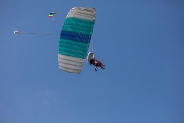 skydivers parachutist on blue sky on sunset