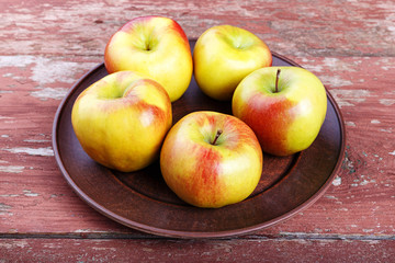 ripe in a dish apples on a wooden table, summer harvest, healthy eating.