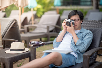 Young Asian man taking photos on bench near the beach, summer holiday and vacation travel concepts