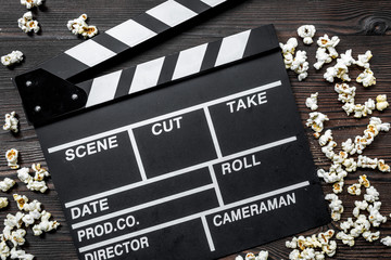 Watching the film. Movie clapperboard and popcorn on wooden table background top view