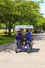 Visitors riding a quad-bicycle along the Governor Tom McCall Waterfront Park in Portland OR, USA