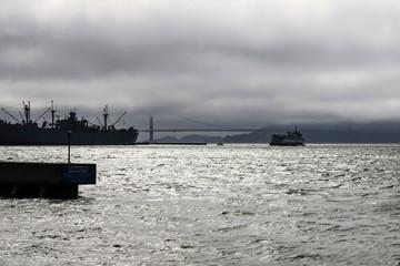 A silhouette image of the Jeramiah O'Brien Liberty Ship and the Golden Gate bridge in San Francisco CA, USA