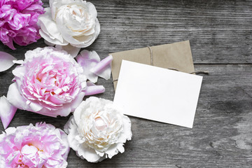 blank greeting card or wedding invitation and envelope with tender peonies flowers