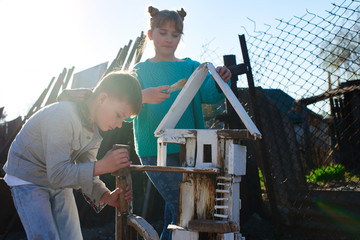A boy and a girl together are building a wooden house