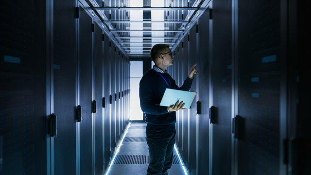 Male IT Engineer Works on a Laptop in front of Server Cabinet at a Big Data Center. Rows of Rack Servers are Seen.