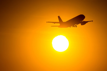Passenger plane is take off during a wonderful sunrise.