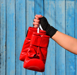 Red boxing gloves hanging on a rope in a woman's hand