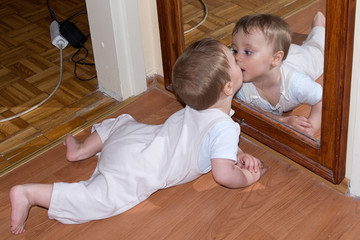 Baby boy kiss in mirror