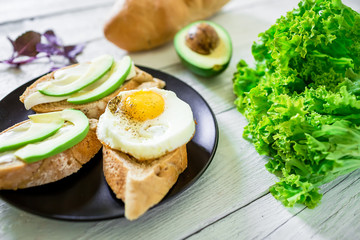 Tasty sandwiches with avocado and egg on plate on white wooden table. Delicious breakfast