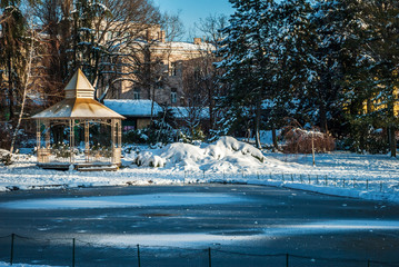 Frozen lake in the  city, with the wooden house by the lake