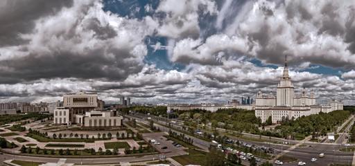 Wide angle panoramic landscape of rainy clouds over sunny spring campus of Lomonosov Moscow State University under blue sky in spring with high dynamic range, bleached colours and soft soft counters
